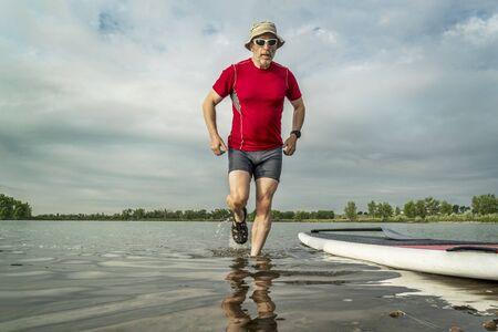 ancianos caminando: palista senior de pie paddleboard en, orilla del lago en el norte de Colorado con un paisaje principios del verano