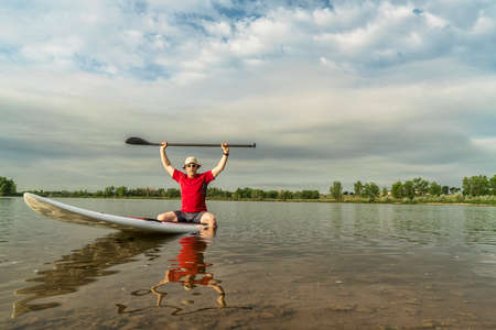 fort collins: senior male paddler sitting on a paddleboard, lake in northern Colorado with an early summer scenery