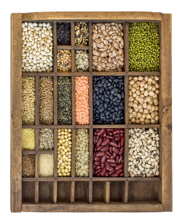 typesetter: assorted beans, lentils, grains and seeds in an old, wooden typesetter drawer isolated on white Stock Photo
