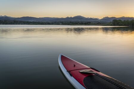 loveland: stand up paddleboard with a paddle on calm lake at dusk with Rocky Mountains in background