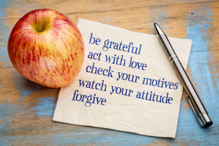 grateful: be grateful and other inspirational phrases - handwriting on a napkin with a fresh apple Stock Photo