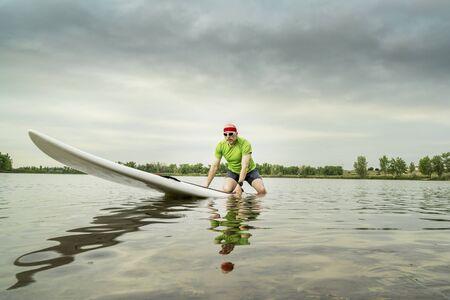 paddleboard: senior male paddler on a paddleboard, lake in northern Colorado,  clody summer morning