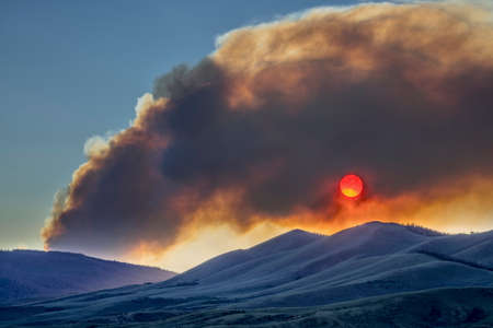 obscuring: wildfire smoke plume obscuring sunset over mountains - North Park, Colorado
