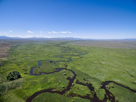 meanders: Illinois River meanders through Arapaho National Wildlife Refuge, North Park near Walden, Colorado, early summer aerial view