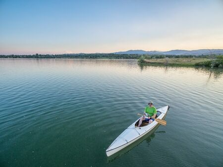 paddler: male paddler is operating a drone from a canoe on a lake, aerial view