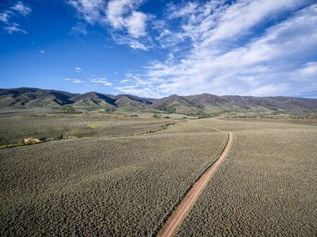 photgraphy: ranch road and Medicine Bow Mountains in North Park near Walden, Colorado - aerial view Stock Photo
