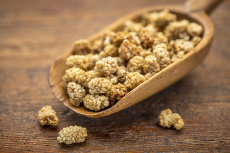 sun-dried white mulberry berries on a rustic wooden scoop against grunge wood, selective focus