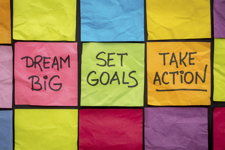 take action: dream big, set goals, take action - motivational advice or reminder on colorful sticky notes