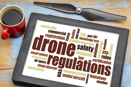 faa: drone regulations (USA, FAA related) word cloud on a digital tablet with a cup of coffee
