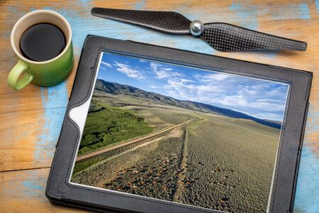 sagebrush: reviewing aerial picture on a digital tablet with a cup of coffee - foothills of Medicine Bow Mountains with a dirt road and cattle, North park, Colorado
