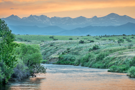St Vrain Creek and Front Range of Rocky Mountains at dusk, St Vrain State Park near Longmont, Colorado