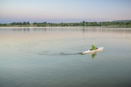 paddler: evening canoe paddling on one of numerous reservoirs along Front Range in Colorado Stock Photo