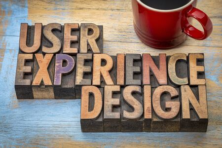user experience: user experience design - word abstract in vintage letterpress wood type with a cup of coffee