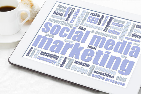 social media marketing concept - a word cloud on a digital tablet with a cup of coffee Stock Photo