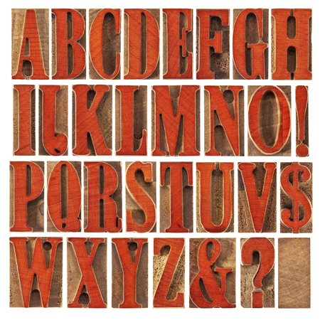 alphabet in modern letterpress wood type printing blocks stained by red ink,  a collage of 26 isolated letters, question mark, exclamation point, ampersand and dollar sign