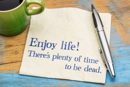Enjoy life! There is plenty of time to be dead. Handwriting on a napkin with a cup of coffee, Stock Photo