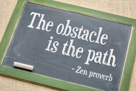 proverb: The obstacle is the path Zen proverb on a vintage slate blackboard with a white chalk against burlap canvas