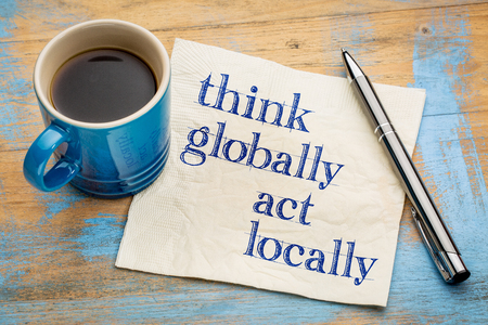 Think globally, act locally reminder - handwriting on a napkin with a cup of espresso coffee Foto de archivo