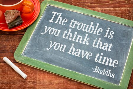 misconception: The trouble is you think that you have time- inspirational quote by Buddha  on a slate blackboard with chalk and cup of tea