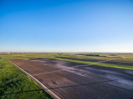 pawnee grassland: aerial view of farmland in eastern Colorado - plowed field, green meadows, dirt road and wind farm at Pawnee National Grassland near Grover Stock Photo