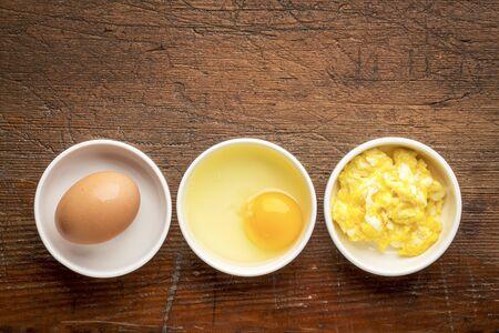 huevos revueltos: abstracta revueltos de huevo - tazones blancos con los huevos contra rústico, resistido madera con un espacio de copia Foto de archivo