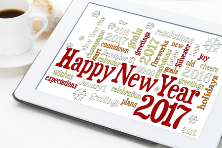 Happy New Year 2017 greetings - word cloud on a digital tablet with a cup of coffee