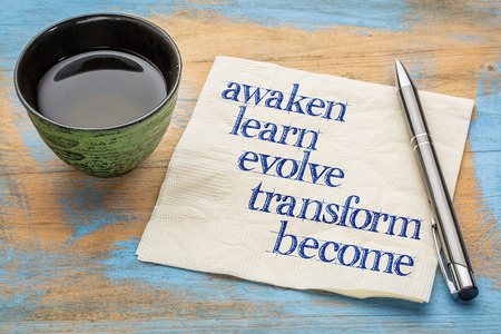 awaken: awaken, learn, evolve, transform and become - inspirational words - handwriting on a napkin with a cup of tea