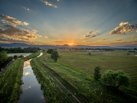 loveland: sunset over Rocky Mountains and foothills with an irrigation ditch - aerial view, northern Colorado near Loveland