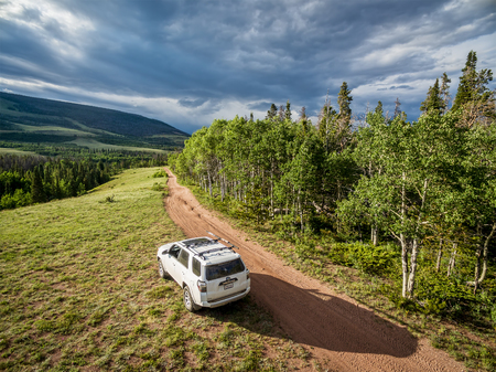dirt road recreation: RED FEATHER LAKES, CO, USA - JUNE 3, 2016: Toyota 4Runner SUV (2016 Trail edition) on a back country road in Colorados Rocky Mountains - aerial view Editorial