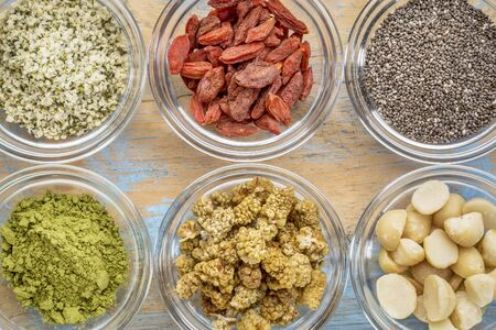 superfood abstract - hemp seeds, goji berries, chia seeds, matcha tea powder, mulberries and macadamia nuts - top view of glass bowls on wood Stock Photo