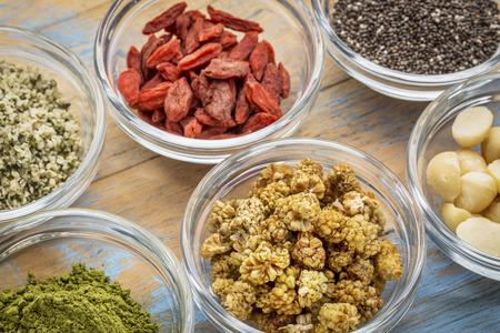 superfruit: superfood abstract - hemp seeds, goji berries, chia seeds, matcha tea powder, mulberries and macadamia nuts -glass bowls on wood