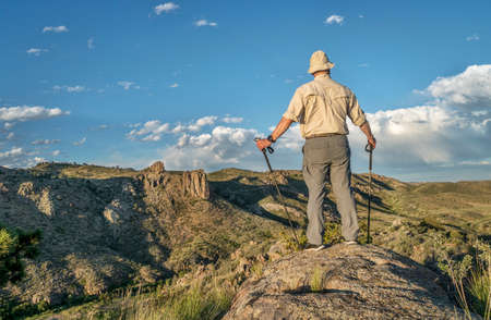 poudre river: male hiker with trekking poles overlooking a mountain valley in northern Colorado - Poudre River North Fork above Halligan Reservoir
