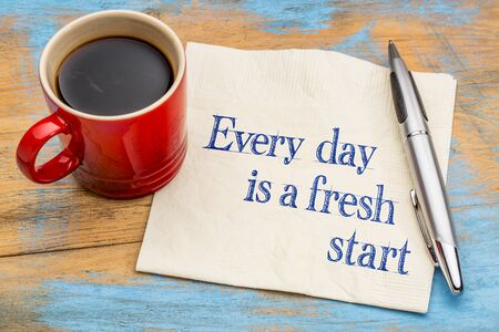 start fresh: Every day is a fresh start - motivational handwriting on a napkin with a cup of coffee.