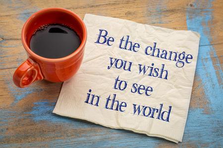 Soyez le changement que vous voulez voir dans le monde - l'écriture d'inspiration sur une serviette avec une tasse de café Banque d'images - 60055392