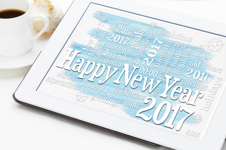 Happy New Year 2017 - word cloud on a digital tablet with a cup of coffee - greeting card
