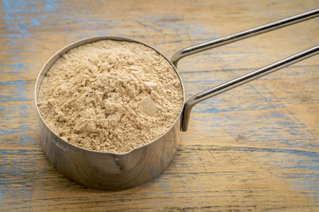 maca: maca root powder on a metal measuring scoop against painted wood