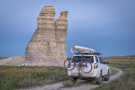 kansas: CASTLE ROCK, KS , USA - JULY 25 2016: Family driving Toyota 4Runner SUV (2016 Trail edition) on summer vacations carrying  a kayak and bike in Kansas back country. Editorial