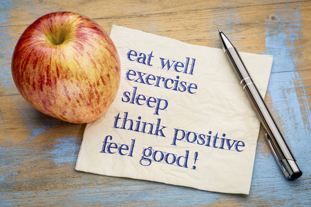 feeling positive: think positive , exercise, eat well, sleep - concept of feeling good - handwriting on a napkin with an apple
