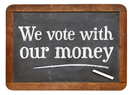 electing: We vote with our money - white chalk text on a vintage slate blackboard Stock Photo