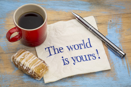 affirmation: The world is yours - a positive affirmation. Handwriting on a napkin with a pen, cup of espresso coffee and cookie against grunge painted wood