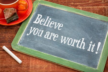 self worth: Believe you are worth it - Motivational advice on a slate blackboard with chalk and cup of tea Stock Photo