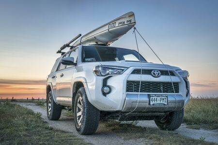 country roads: CASTLE ROCK, KS , USA - JULY 25 2016: Toyota 4Runner SUV (2016 Trail edition) with a canoe (Sea Wind by Kruger Canoes) on roof racks driving during summer vacations on Kansas  back country roads