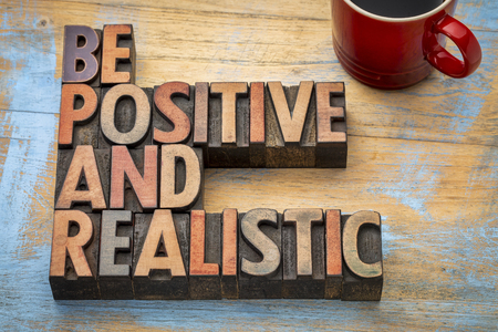 be positive and realistic - motivational text in vintage letterpress wood type printing blocks Banco de Imagens