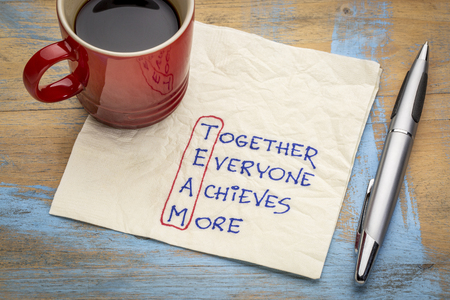 TEAM acronym (together everyone achieves more), teamwork motivation concept - a napkin doodle with a cup of coffee