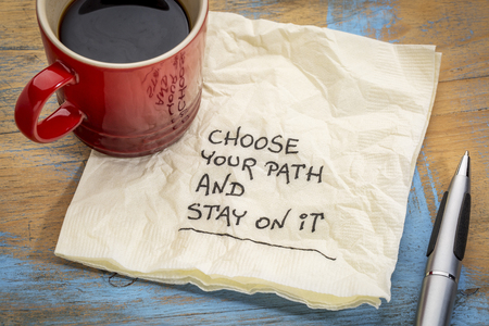 set goals: Choose your path and stay on it - motivational handwriting on a napkin with a cup of coffee Stock Photo