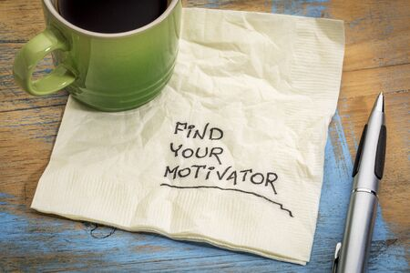 motivator: find your motivator advice - handwriting on a napkin with a cup of coffee Stock Photo