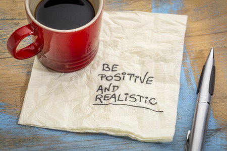 be positive and realistic - handwriting on a napkin with a cup of coffee Banco de Imagens