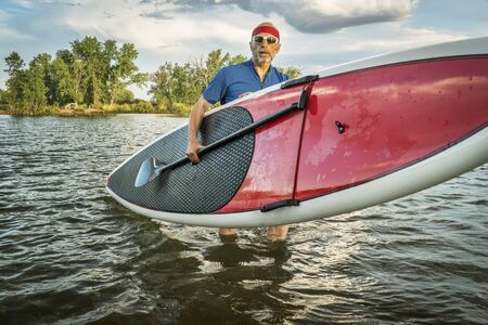 hist: senior male with hist stand up paddleboard on a lake in Colorado Stock Photo