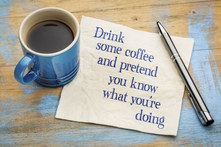 pretend: Drink some coffee and pretend that you know what youre doing - handwriting on a napkin with a cup of espresso coffee