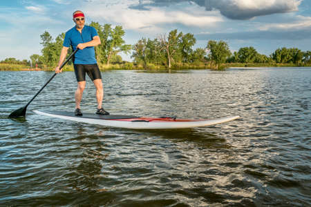 paddler: senior male on stand up paddleboard on a lake in northern Colorado